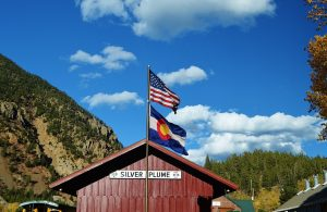 Colorado flag and the American flag flying over a covered bridge